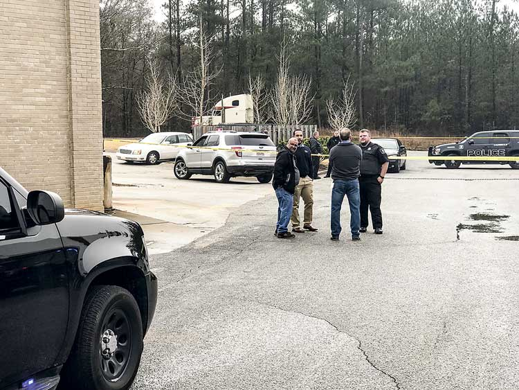 Tyrone officers interview witnesses in the Monday robbery of the O'Reilly's Auto Parts store on Tyrone Road near Ga. Highway 74 in Tyrone. No one was injured in the incident where shots were fired. Photo/Ben Nelms.