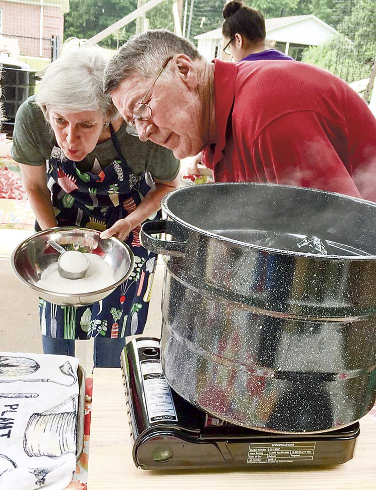 Hopewell UMC members Janet Lester and Bob Golden carefully measure out the right amount of sugar to be used in canning the strawberries. Photo/Sandy Golden.